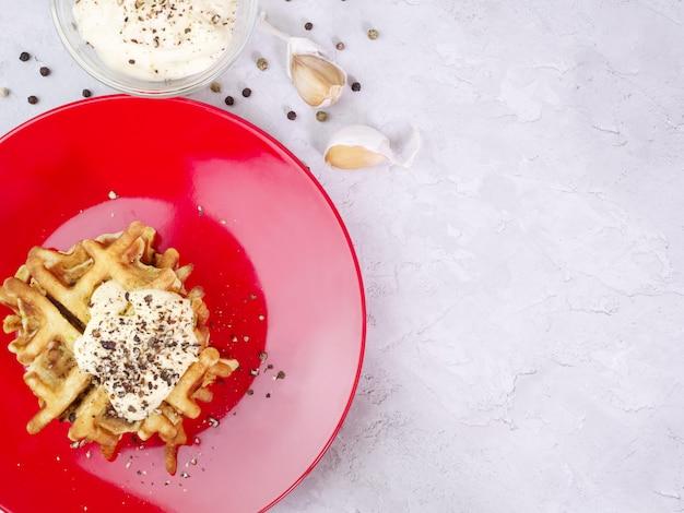 Waffles de abobrinha num prato vermelho com molho e especiarias