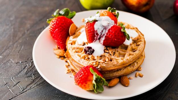 Waffles de alto ângulo com morangos e iogurte