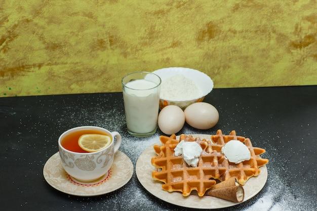 Waffles de alto ângulo vista no prato com chá, ovos, farinha na superfície escura e texturizada. horizontal