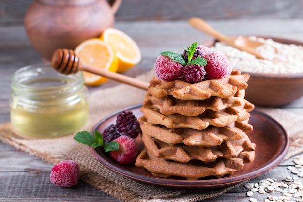 Waffles de aveia caseiros com frutas e mel em uma velha mesa de madeira