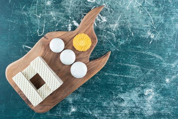 Waffles de baunilha crocantes e biscoitos na placa de madeira.