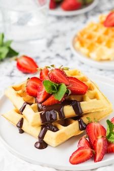 Waffles de bélgica com cobertura de chocolate e morangos. comida de café da manhã