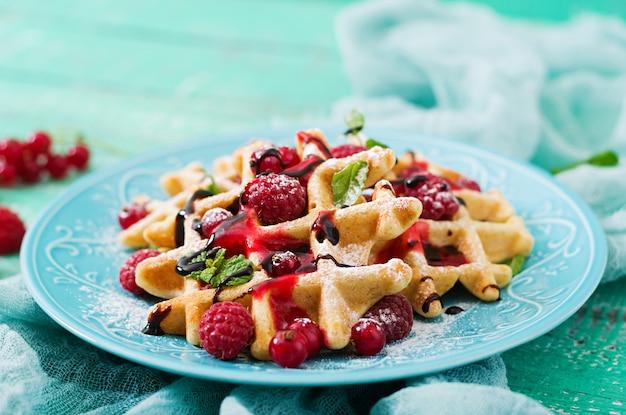 Waffles de bélgica com framboesas e calda em um prato.