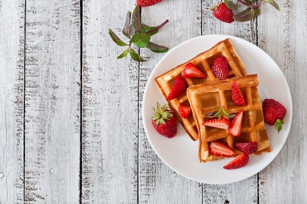 Waffles de bélgica com morangos e hortelã na chapa branca