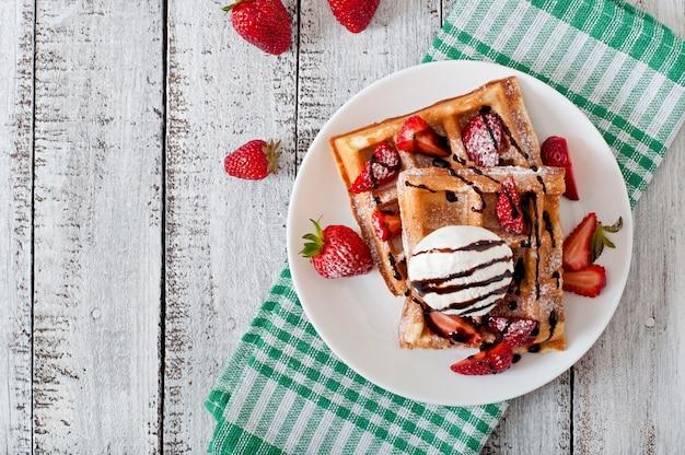 Waffles de bélgica com morangos e sorvete no prato branco