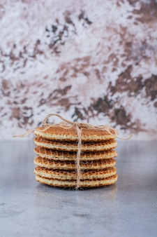 Waffles de caramelo amarrados com laço de juta isolado em uma superfície de pedra