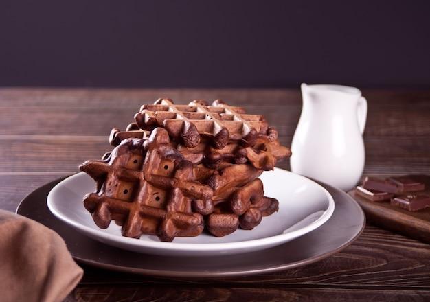 Waffles de chocolate caseiros na mesa de madeira.