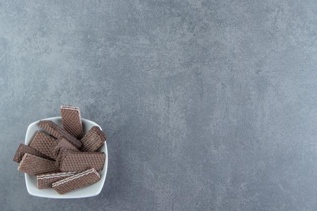 Waffles de chocolate crocantes em uma tigela branca.