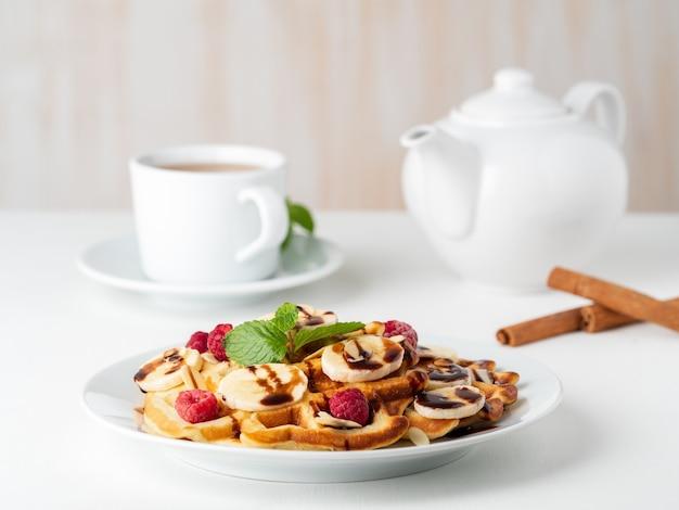 Waffles de coalhada belga com framboesas, banana, xarope de chocolate. café da manhã