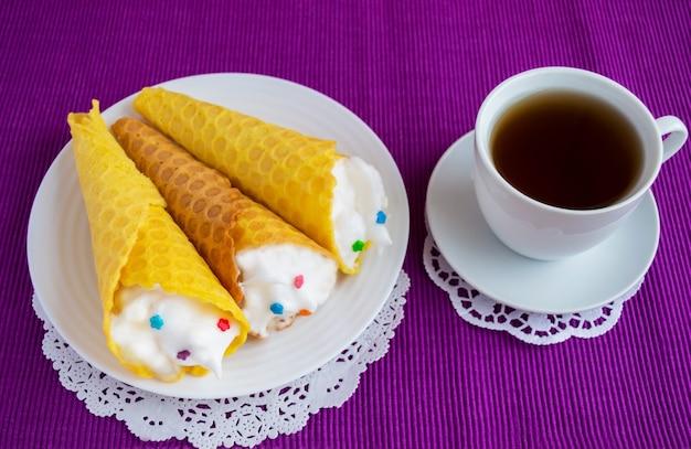 Waffles de mel fresco enrolados em um cone com um creme suave em um guardanapo colorido e uma xícara de chá
