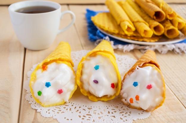 Waffles de mel fresco enrolados em um cone com um creme suave em uma mesa de madeira e uma xícara de chá