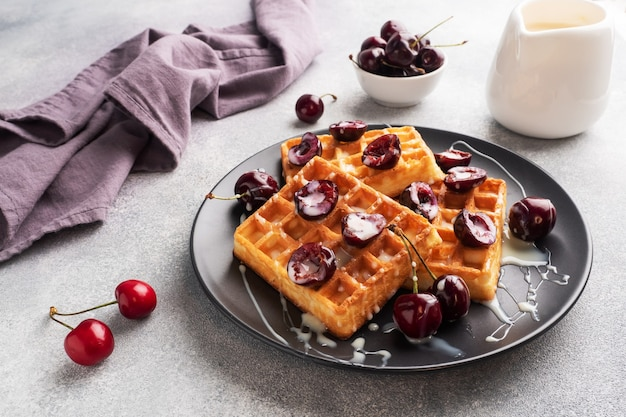 Waffles de pregas belgas com cerejas frescas e creme num prato.