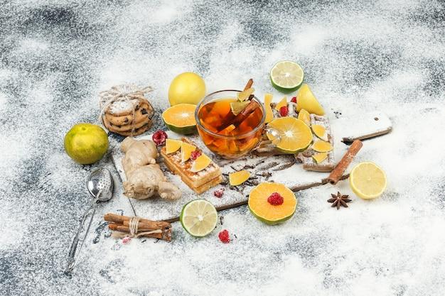 Waffles de vista de alto ângulo e bolachas de arroz na placa de corte branca com coador de chá de ervas, frutas cítricas, canela e chá na superfície de mármore cinza escuro. horizontal