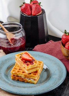 Waffles de vista lateral com creme de baunilha, morango e geléia em cima da mesa