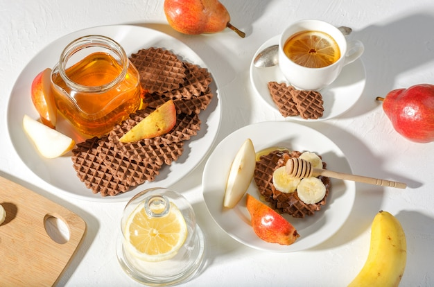 Waffles do chocolate com pera, mel e a banana vermelhos para o café da manhã no fundo branco.