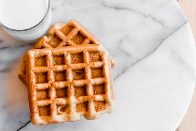 Waffles doces belgas ou vienenses frescos e um copo de leite no fundo de mármore branco.