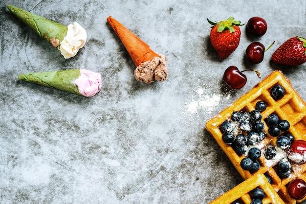 Waffles doces com saborosas frutas vermelhas cheias de vitaminas saudáveis com alguns sorvetes com waffle, sobre fundo de pedra azul com espaço de cópia de texto.