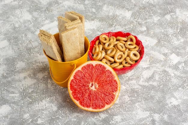 Waffles e biscoitos com grapefruit na superfície branca de vista frontal