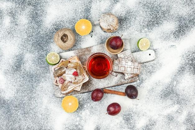 Waffles e bolachas de arroz com frutas cítricas, canela e biscoitos na superfície de mármore cinza escuro. horizontal