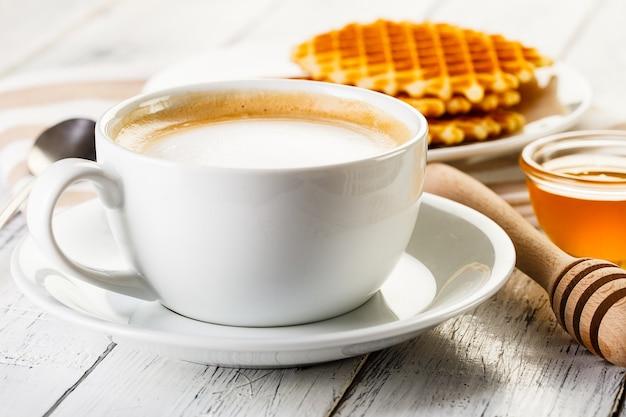 Waffles e café na mesa de madeira branca