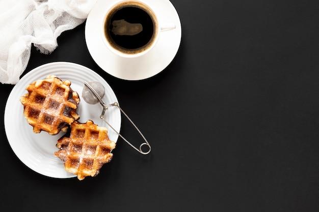 Waffles e café na mesa preta