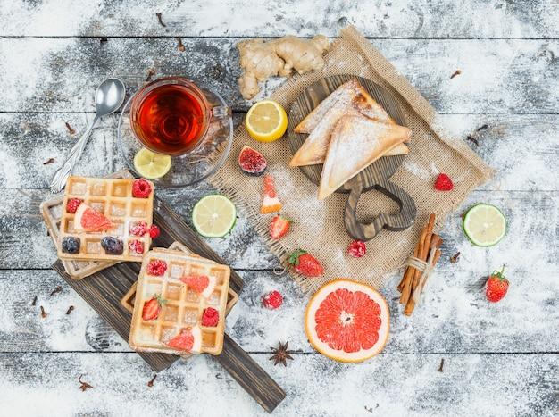 Waffles e chá na tábua de madeira com frutas e frutas cítricas