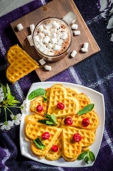 Waffles e chocolate quente com marshmallows em uma manta