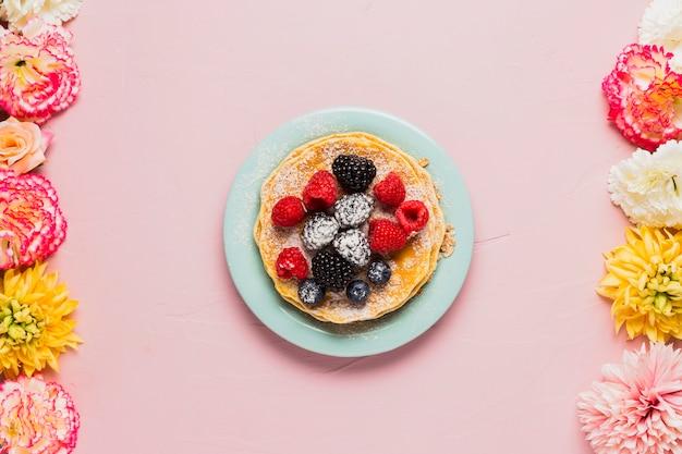 Waffles e frutos silvestres em fundo rosa