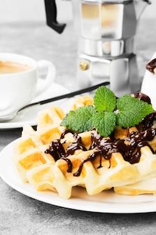 Waffles em chapa branca com chocolate e menta, café, molho de barco com chocolate