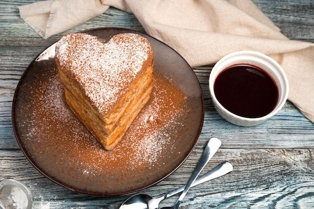 Waffles em forma de coração são polvilhados com açúcar de confeiteiro e cacau em um fundo cinza.