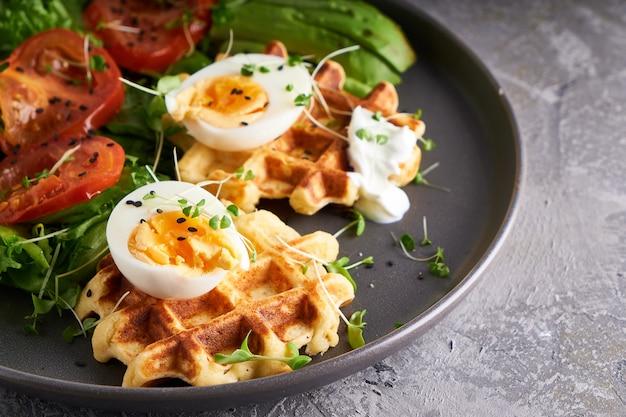Waffles, ervas, tomates, salada, ovos e temperos servidos em um prato