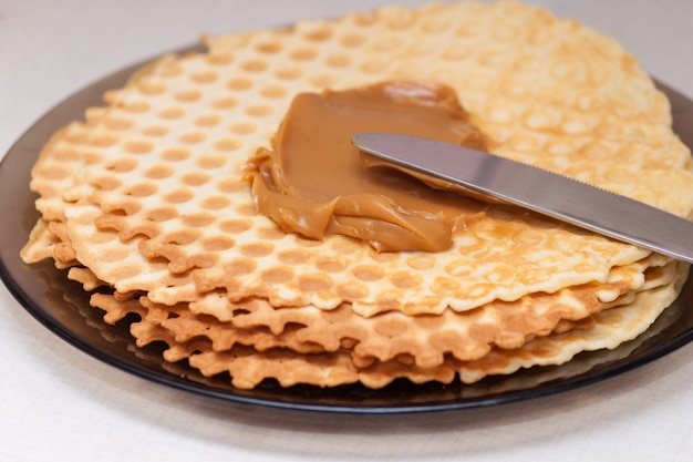 Waffles finos caseiros com leite condensado no prato