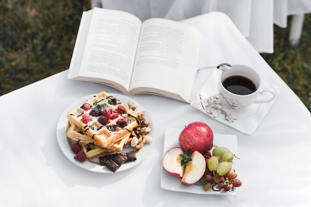 Waffles; frutas; xícara de café e um livro aberto na mesa branca