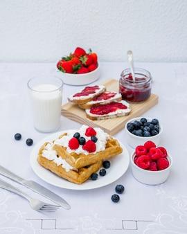 Waffles, leite e frutas vermelhas na mesa