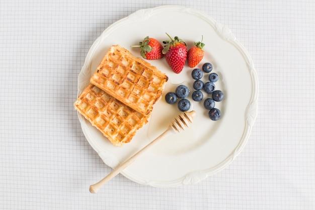Waffles; morango e mirtilos na placa de cerâmica sobre a toalha de mesa