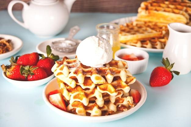 Waffles recém-assados caseiros com morangos, mel e sorvete.