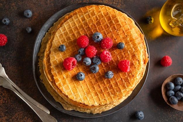 Waffles redondos crocantes dourados servidos no prato com frutas vermelhas. fechar-se.