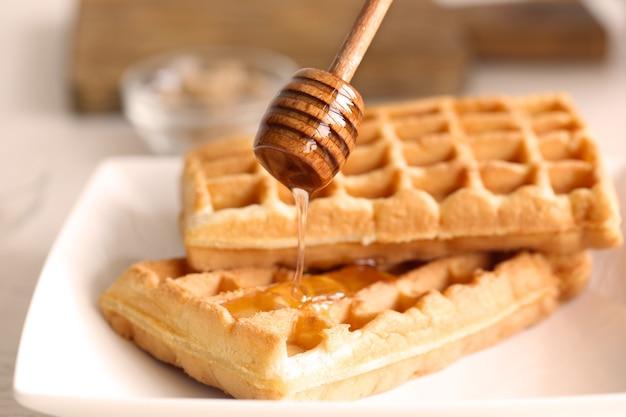 Waffles saborosos com mel no prato, closeup