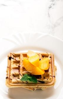 Waffles vienenses com pêssegos e chocolate