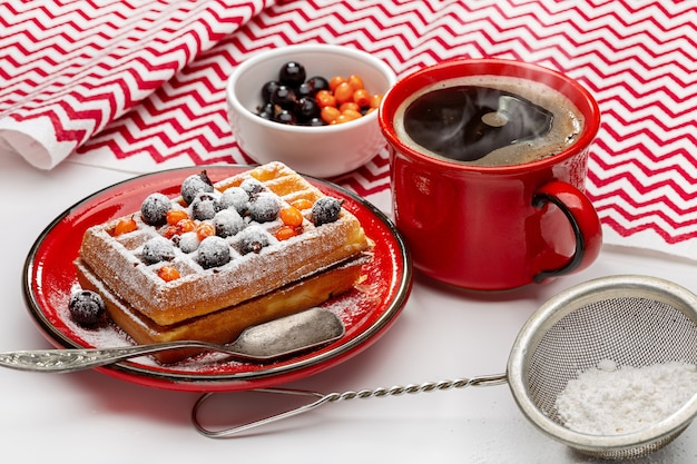 Waffles vienenses polvilhados com pó e decorados com frutas vermelhas. café quente na xícara vermelha.