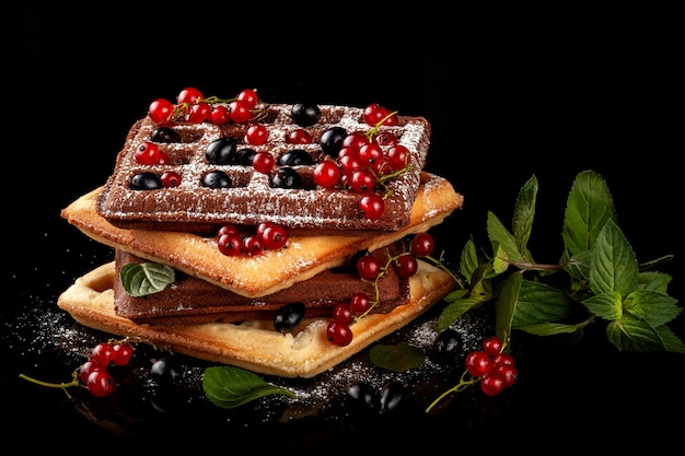 Waffles vienenses recém-assados repousam sobre uma mesa preta.