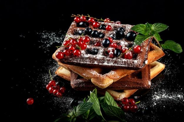Waffles vienenses recém-assados repousam sobre uma mesa preta. Foto Premium