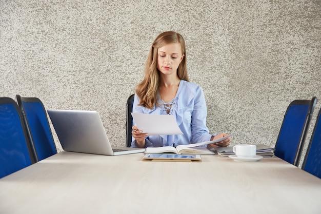 Waistup de negócios jovem senhora sentada na mesa no escritório olhando para o documento