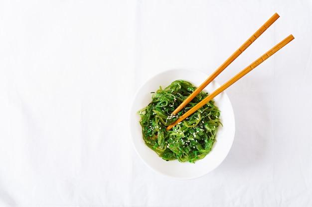 Wakame chuka ou salada da alga com as sementes de sésamo na bacia no fundo branco.