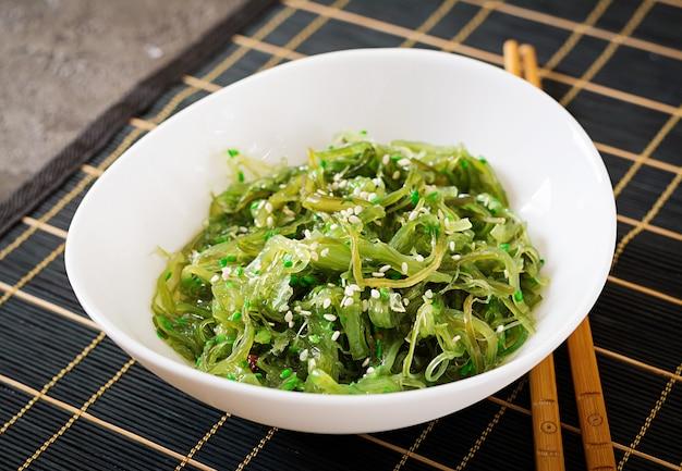 Wakame chuka ou salada de algas com sementes de gergelim na tigela sobre fundo preto.