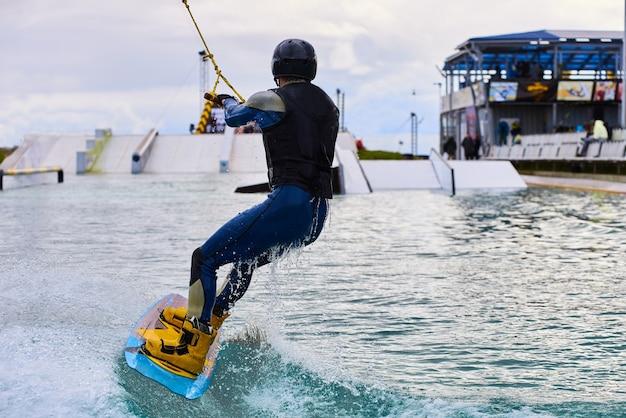 Wakeboarder com corpo forte de pedalada em wake park