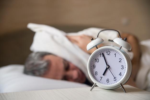 Waked up homem deitado na cama desligando um despertador no meio da manhã