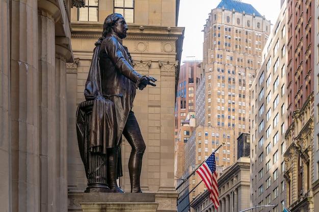 Wall street no distrito financeiro de manhattan e a estátua de washington em primeiro plano
