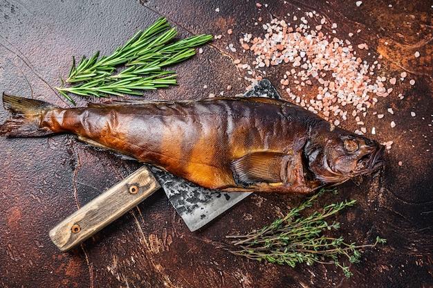 Walleye de peixe fumado quente ou poleiro de lúcio em uma placa de madeira com ervas. fundo escuro. vista do topo.