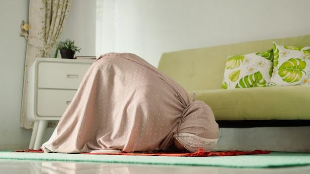 Wanita muçulmano melakukan salat dengan gerakan sujud mengenakan mukenah